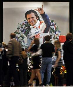 Floral Display in front of enlarged photo of Dan Wheldon at his Celebration of Life
